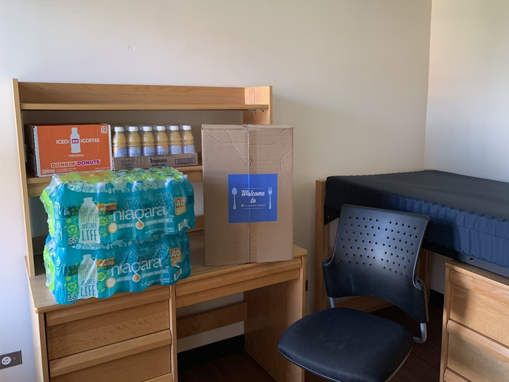 A dorm room that has a Welcome Box along with a supply of water, juice, and coffee sitting on a desk.