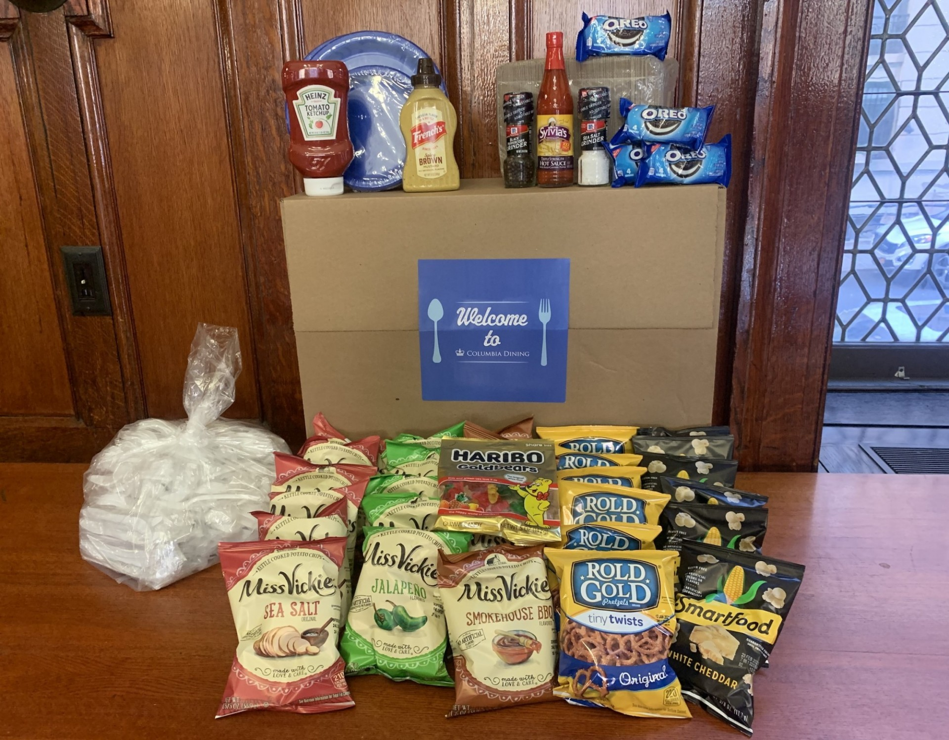 A Welcome Columbia Dining Box with all of its contents - snacks, disposable flatware, condiments and more.